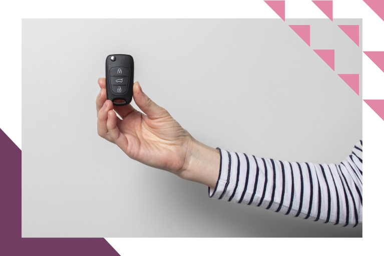 arm with a long-sleeved striped shirt holding wireless car key